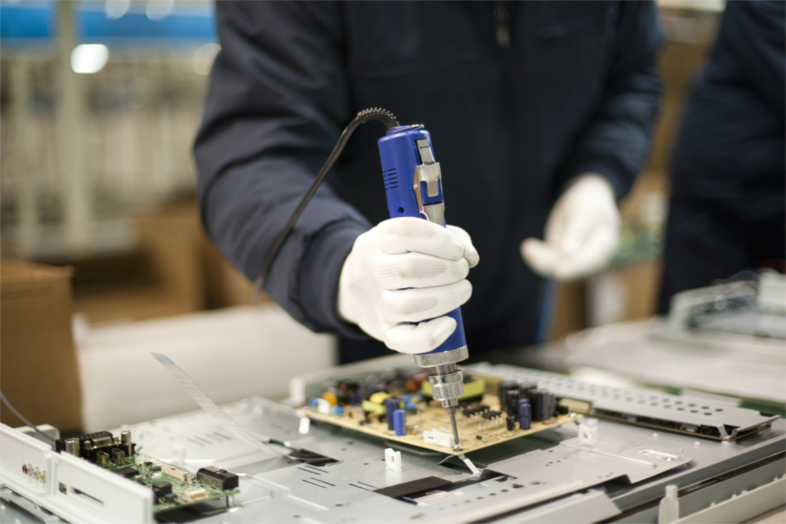 Factory Worker Screwing Mount to Circuit Board